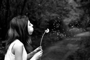Woman making wish on dandelion